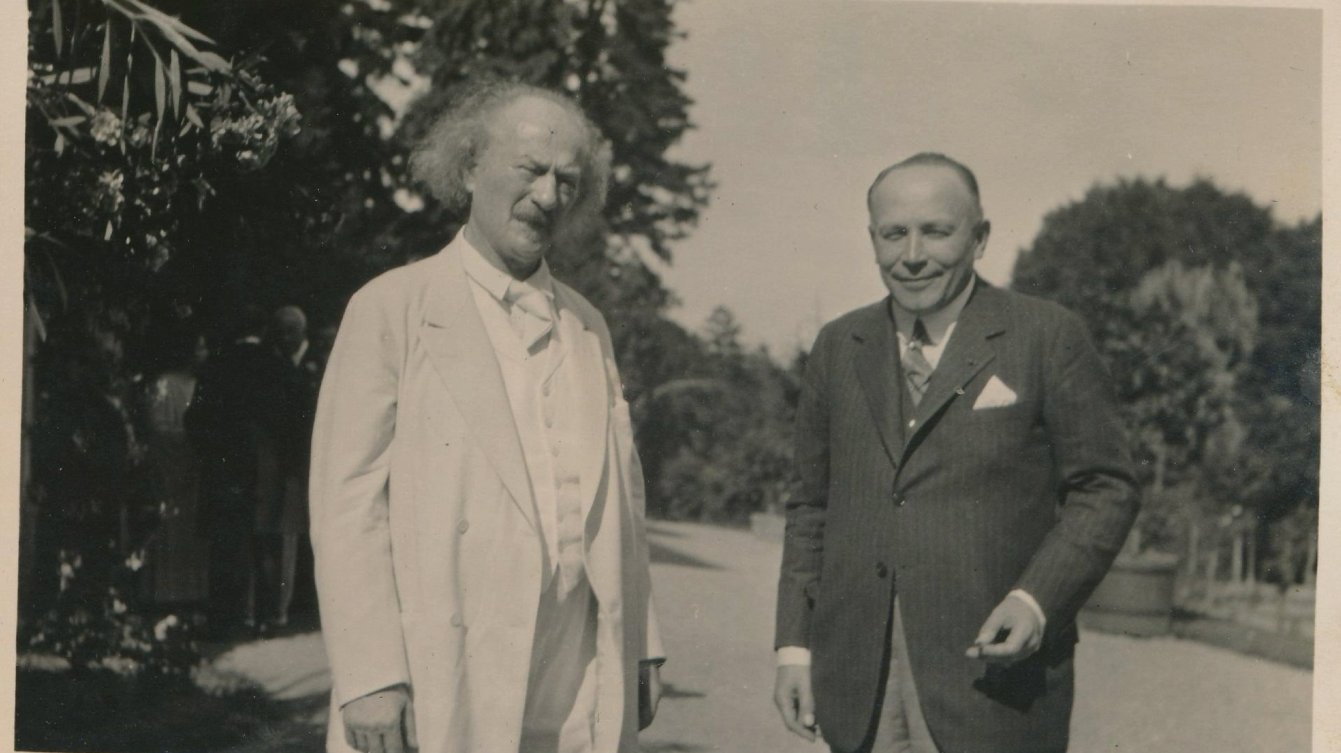 Black and white picture of two elegantly dressed men (one of them Ignacy Jan Paderewski) standing on the road, trees in the background. - grafika artykułu