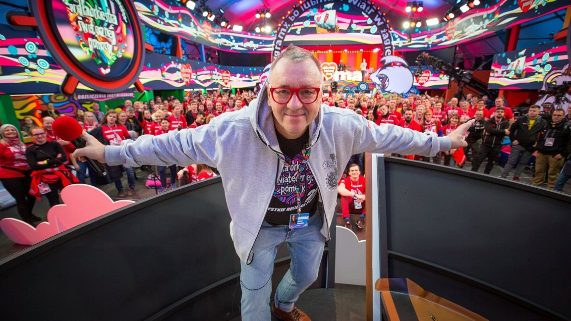 Colourful photo of Jurek Owsiak - creator of Grand Orchestra of Christmas Charity, taken in a TV studio. In the background people mostly dressed in red t-shirts with Grand Orchestra of Christmas Charity logo. - grafika artykułu
