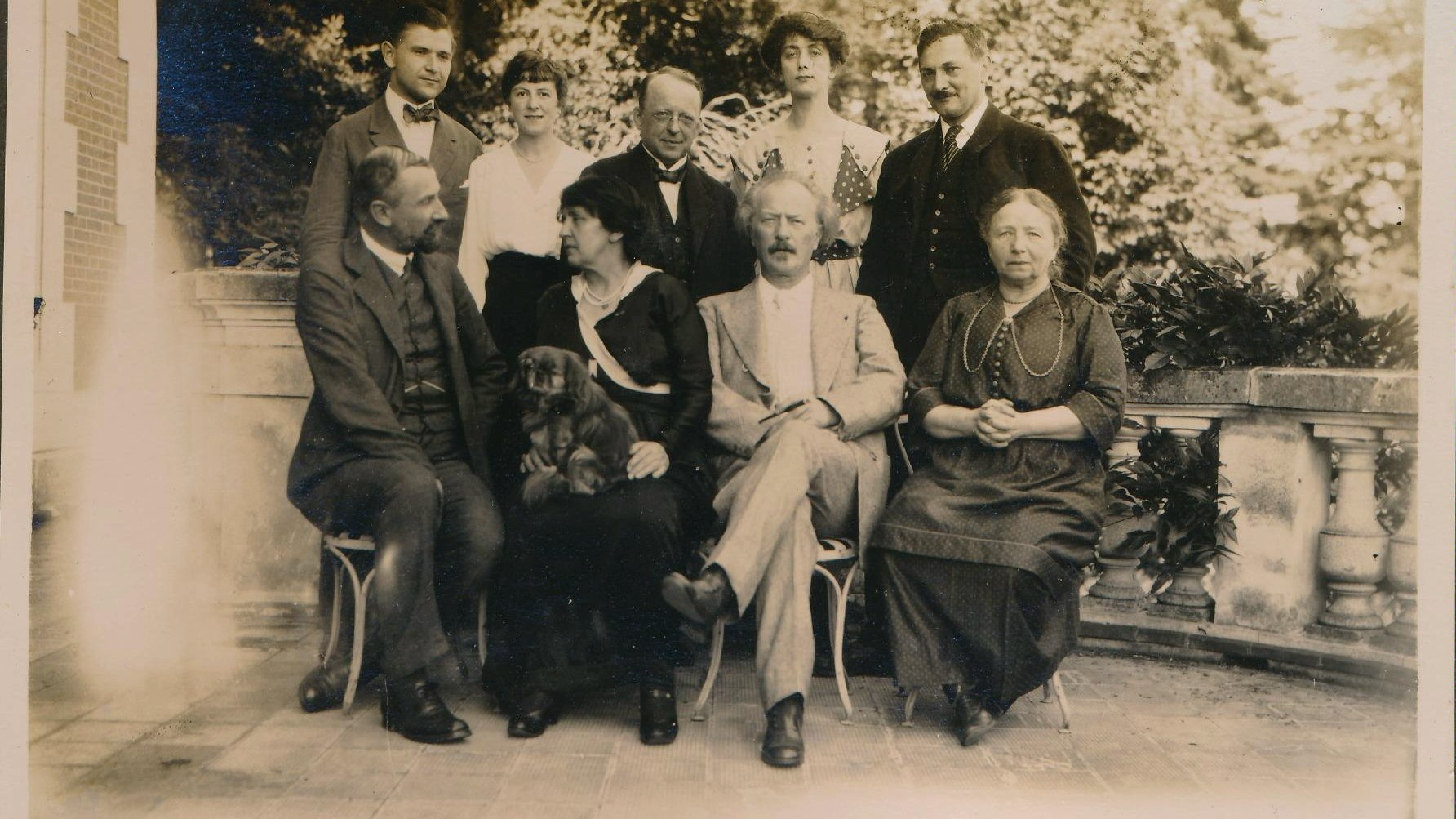 Picture of group of people, posing to the camera. Four of them are sitting, five is standing. The elements of a building and trees in the background.