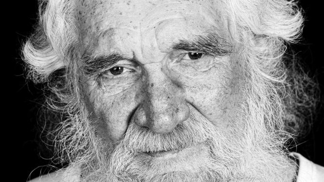 Black and white picture of an elderly man's face with grey hair and grey beard