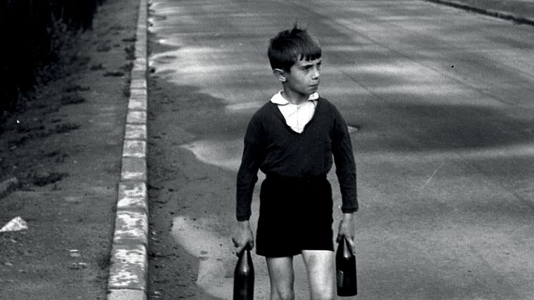 Black and white picture of a boy walking along a road and holding two bottles in his hands. He is dressed in old-fashioned clothes.