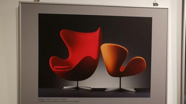 Photo of a picture hanging on the wall: two modern armchairs, one red and one orange