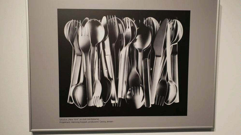 Black and white photo of a picture hanging on the wall presenting cutlery