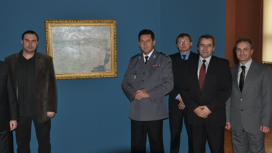 "Five men looking at the camera, in the background the picture ""Beach in Pourville"" in golden frame on blue wall"