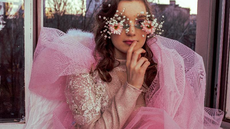 Picture of young woman dressed in pink garment in glasses decorated with flowers.